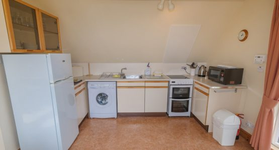 kitchen with hob, oven, fridge/freezer, microwave and washing machine