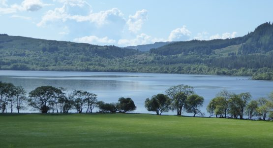 sun shining on Loch Awe with trees and a field
