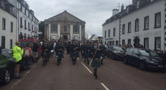Kilted pipers marching down the main street in Inveraray