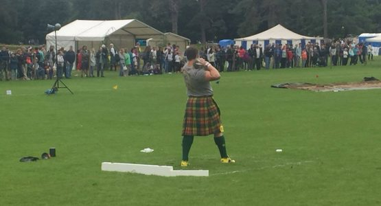 Man a kilt throwing a 16lb stone at highland games